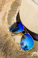 Sunglasses and sun hat on the sand beach