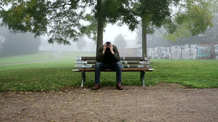 man expressing sorrow on bench in park