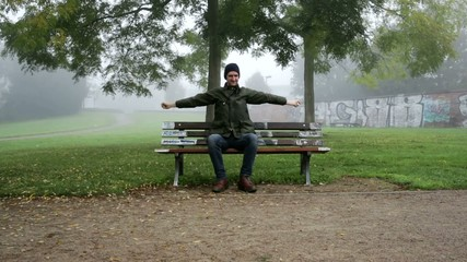man stretching on bench at foggy morning