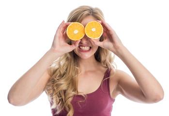Frau hält Orangenscheiben auf die Augen