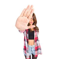 Brunette girl making stop sign over white background