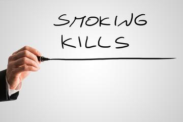 Close up of the hand of a man writing Smoking kills