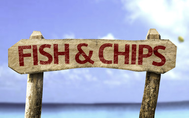 Fish & Chips wooden sign with a beach on background