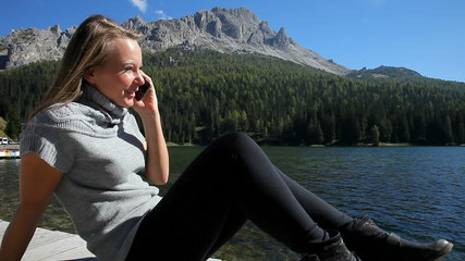 Happy woman in vacation in mountain on the phone