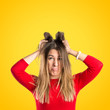 Pretty girl frustrated over yellow background