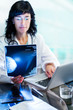 Female doctor analyzing  mammogram x-ray.