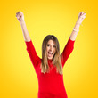 Young woman winner on yellow background