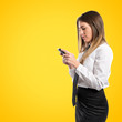 Young businessmen with his mobile over yellow background.