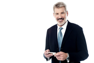 Smiling businessman with cellphone