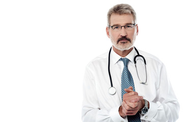 Senior male doctor keeping hands clasped