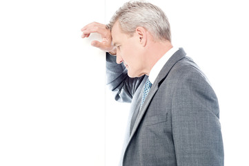 Worried businessman leaning head on wall