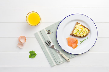 Top view of healthy breakfast with scrambled eggs on toast