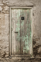 Old timber door in the scuffed wall