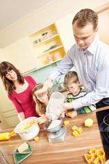 Junge Eltern backen in der Küche mit ihren Kindern