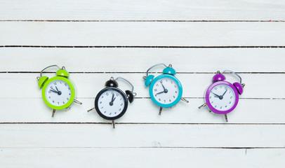 Four alarm clocks on white background.