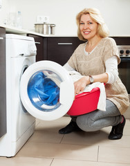 Home laundry. Housewife using washing machine at home