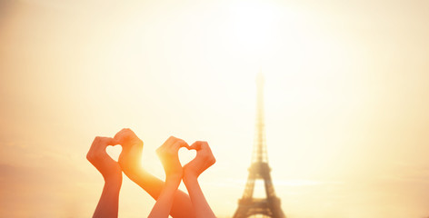 Two lovers showing heart shapes with hands and parisian Eiffel t