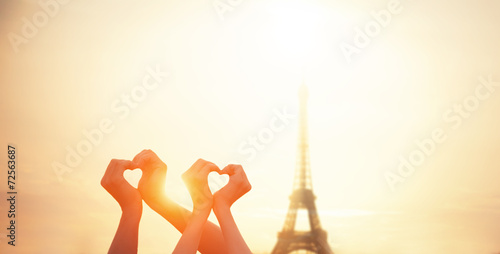 Two lovers showing heart shapes with hands and parisian Eiffel t - 72563687