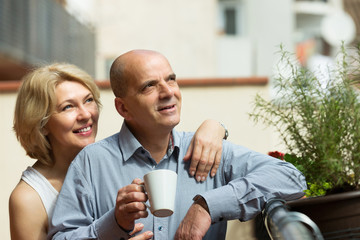 Couple drinking coffee at balcony