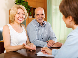 Mature couple with insurance agent