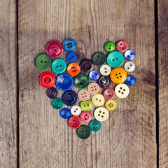Vintage buttons in the shape of a heart on a wooden  background
