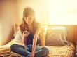 Leinwanddruck Bild - tech savvy asian teen girl using smart phone in bed
