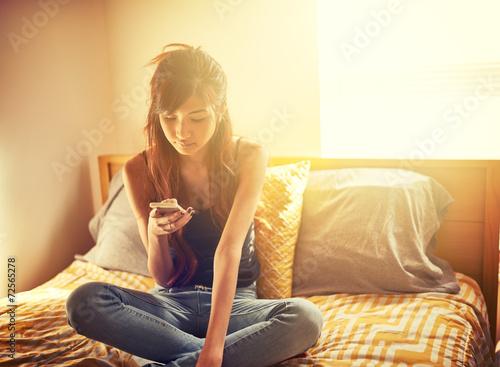 Leinwanddruck Bild tech savvy asian teen girl using smart phone in bed