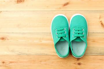 Green shoes on wooden floor.