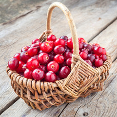 Fresh red cranberries in wicker basket on rustic table