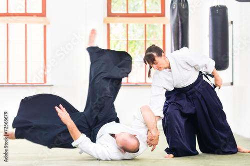 Fototapeta Man and woman fighting at Aikido martial arts school
