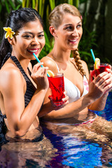 Women at Asian hotel pool drinking cocktails
