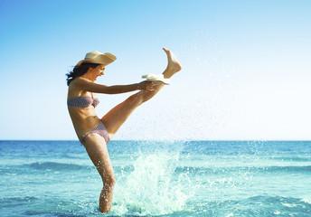 Woman kicking sea water