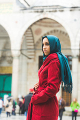 Young Arabian Woman wearing Veil in front of a Mosque