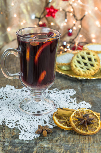 Mulled wine, mince pies and spices on wooden background
