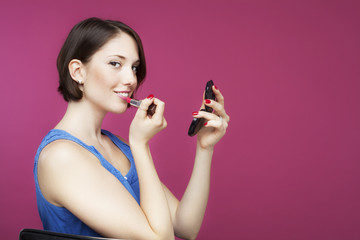Beautiful young woman on pink background, putting on make up.