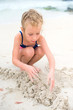 Little girl playing with sand on the beach.