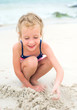 Little smiling girl playing with sand on the beach.