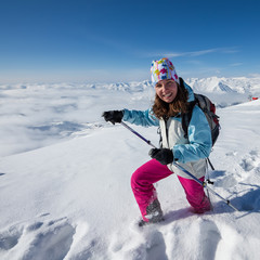 Hiker posing at top of snowy mountain during sunny day