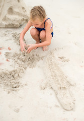 Little girl playing on the beach. Building sand crocodile.