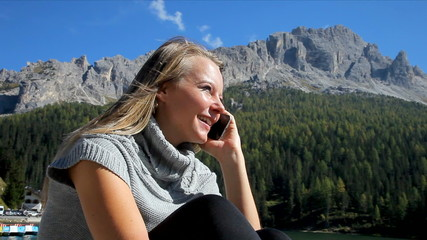 Happy blond woman talking on the phone with boyfriend