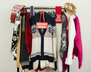 Winter sweaters with a big Christmas sale sign. Clearance rack.