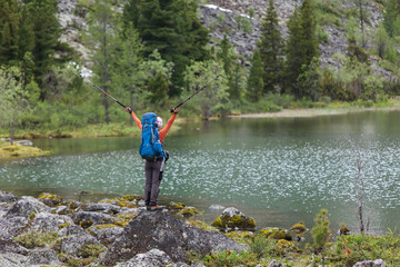 Backpacker posing nearby mountain lake in Altai mountains, Russi