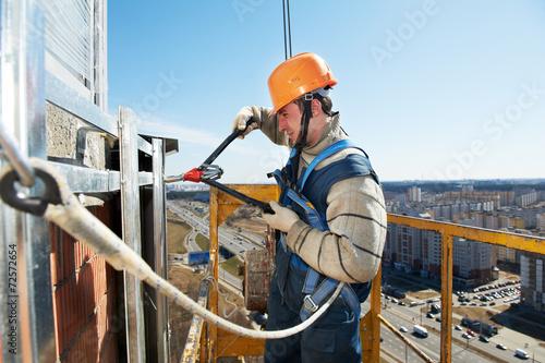 Leinwanddruck Bild Worker builders at facade tile installation