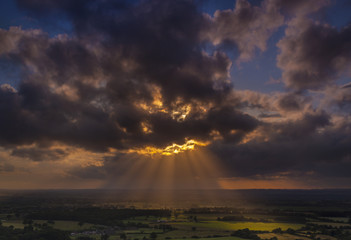 Crepuscular rays of sunlight shine onto fields in Dorset