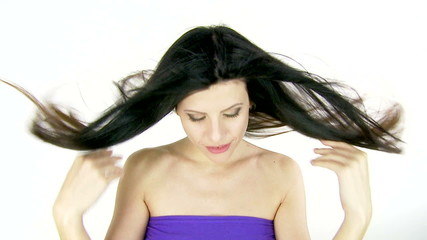 Woman playing with long hair in the wind in studio slow motion