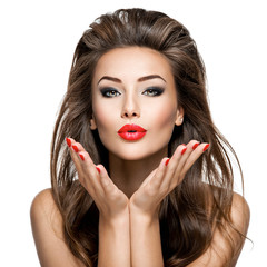 Beautiful woman with long hair and bright make up sends a kiss s