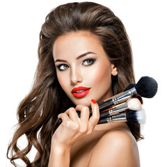 Beautiful sexy young woman holds the makeup brushes at face