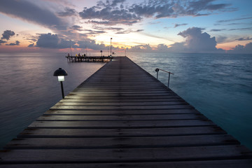 Wooden pier to Indian ocean ath the sunset