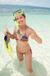 Happy woman snorkeling  and having fun in water holding fins