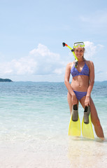 Happy woman snorkeling  andsmiling in water holding fins